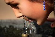 female teen drinks water from a water fountain