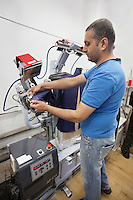 Man adjusting shirt on laundry dummy machine at launderette