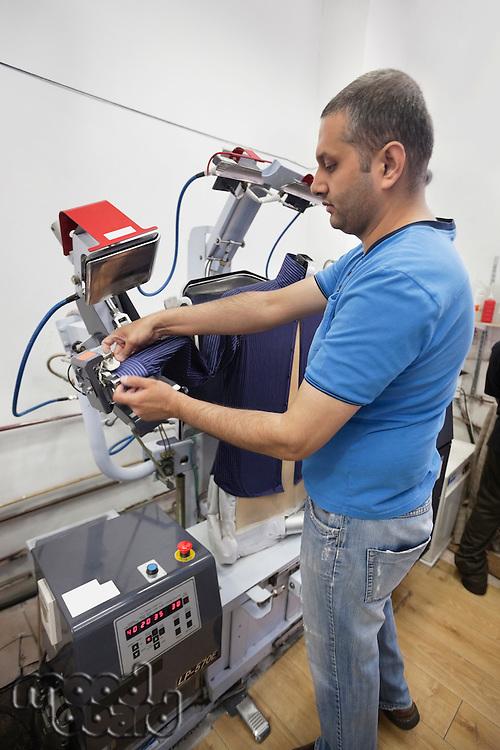 Man adjusting shirt on laundry dummy machine at launderette