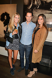 Left to right, ARIANA STEIN, CHRIS KELLNER and ANOUSHKA LOFTUS at a private view of photographs by Marc Lagrange at Heist, 43 Linden Gardens, London on 2nd October 2014.