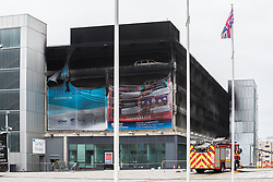 UK OUT © Licensed to London News Pictures . 01/01/2018. Liverpool, UK. Scene at the Liverpool Echo Arena car park where firefighters are working to extinguish a fire that started late on New Year's Eve and that destroyed all 1,400 cars parked in the multi-story car park. The Liverpool International Horse Show taking place at the Arena was abandoned and people and horses evacuated as dozens of fire crew worked to control the blaze . Photo credit: Joel Goodman/LNP