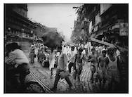 Cobblestone street, porters and tram rails, Calcutta, India.