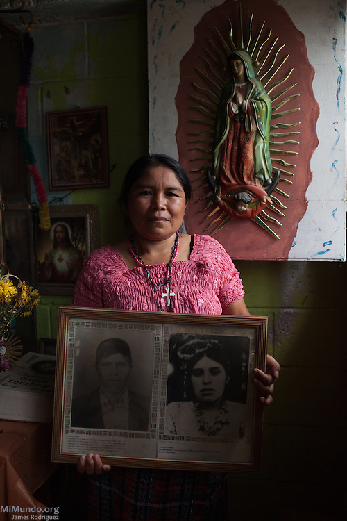 Paulina Chen Osorio, 44, survivor from Rio Negro, holds photographs of her late parents Pedro Chen and mother Narcisa Osorio Lopez inside a special room-turned-shrine in her home. She hopes the Forensic Anthropology Foundation of Guatemala (FAFG) identifies and returns her father Pedro Chen, and brothers Daniel (15), Carlos (7) and Francisco (6) who were either killed or abducted during the May 14, 1982, Los Encuentros Massacre and possibly exhumed in 2012 from grave XV at the UN's CREOMPAZ training center, formerly Coban's Military Zone 21. During the massacre, Guatemalan soldiers and civil patrolmen killed 79 community members from Rio Negro who were hiding here after the previous two massacres of February and March of the same year. Eyewitnesses assured that at least 15 other community members were abducted in a helicopter. As of May 2016, CREOMPAZ's grave XV has rendered positive DNA matches of the remains of two victims abducted in the helicopter on such day. Paulina is not sure if her father and siblings were killed in Los Encuentros or taken by Helicopter. Her mother Narcisa Osorio Lopez was killed along with 176 other women and children during the March 13, 1982, massacre at Pak'oxom peak near Rio Negro. Paulina lives in Pacux, the resettlement village outside Rabinal where the former Achi Mayan residents of Rio Negro were forcibly relocated after the massacres and destruction of their village and dozens more due to the flooding of the Chixoy river basin and construction of the Chixoy Hydro-electric project. Pacux, Rabinal, Baja Verapaz, Guatemala. May 20, 2016.