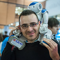 Lyon, France - 19 March 2014: a man brings NAO Robot by Aldebaran on his shoulders at Innorobo 2014, the biggest fair in Europe for robotics.