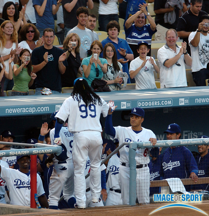 Los Angeles Dodgers outfielder Manny Ramirez (99) is welcomed to the dugout after his first homerun as a Dodger during a 4 to 2 win over the Arizona Diamondbacks at Dodger Stadium on August 2, 2008 in Los Angeles, California.