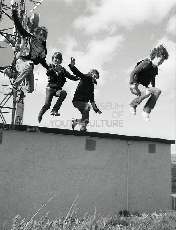 Group of young people jumping off wall.