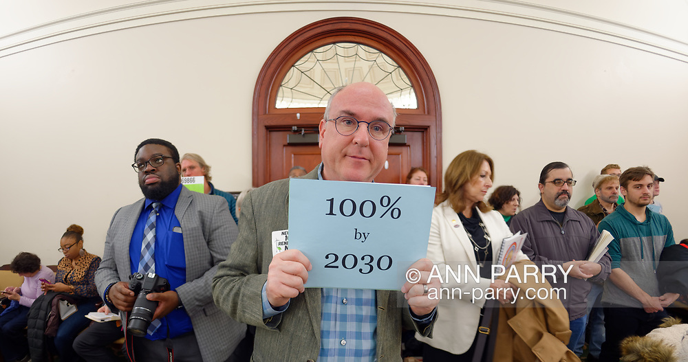 Mineola, New York, USA. 15th Feb, 2019. ERIC WELTMAN, Brooklyn, a Senior Organizer for Food & Water Watch in New York, is holding a blue card with 100% by 2030  on it, referring to goal of 100% clean energy by 2030, during NYS Senate Public Hearing on Climate, Community & Protection Act, Bill S7253, sponsored by Sen. Kaminsky, Chair of Senate Standing Committee on Environmental Conservation. This 3rd public hearing on bill to fight climate change was on Long Island.Long Island.