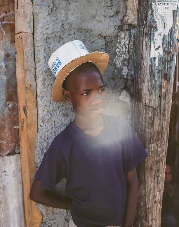 A boy wearing a top hat he made himself out of cardboard poses for a portrait on Thursday, December 18, 2014 in Port-au-Prince, Haiti. Fort National was among the hardest hit areas of Port-au-Prince in the 2010 earthquake, but rebuilding has been slow to non-existent. Residents still mostly lack electricity and running water.
