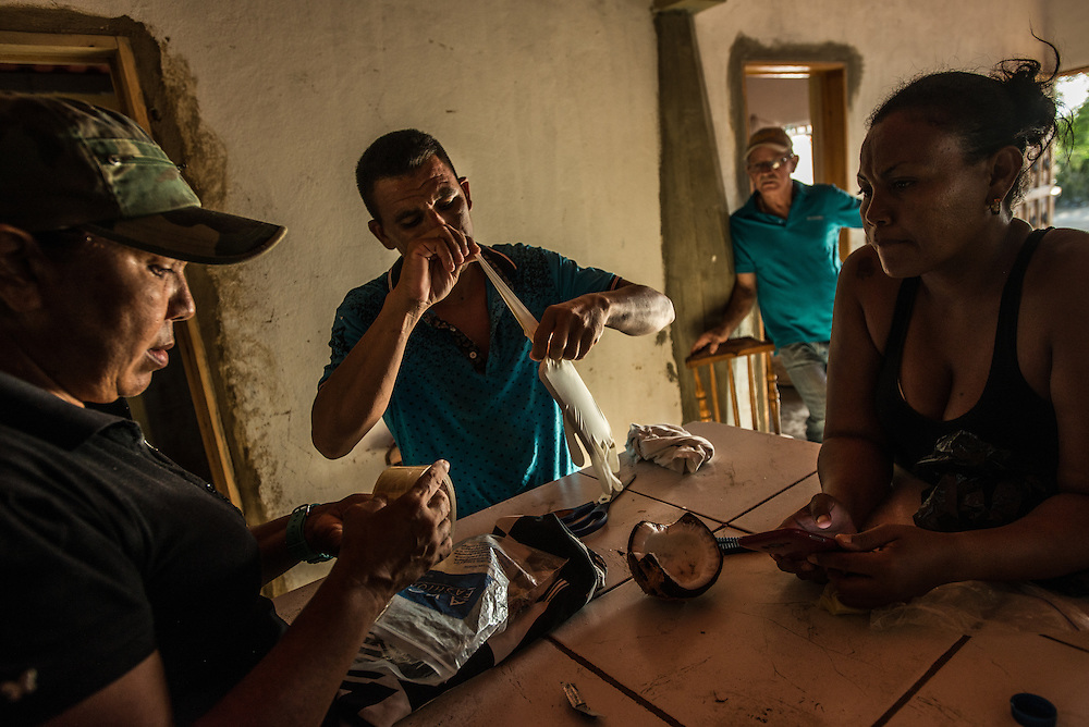 FALCÓN, VENEZUELA - SEPTEMBER 26, 2016: Undocumented migrants put their cell phones in latex gloves wrapped in packaging tape in effort to waterproof them for the wet boat ride from Venezuela to Curaçao.  Migrants here have mortgaged property, sold kitchen appliances and even borrowed money from the same smuggling rings that pack them on the floorboards alongside drugs and other contraband. The journey to Curaçao takes them on a 60-mile crossing filled with backbreaking swells, gangs of armed boatmen and coast guard vessels looking to capture migrants and send them home. Then, after being tossed overboard and left to swim ashore, they hide in the brush to meet contacts who spirit them anew into the tourist economy of this Caribbean island. They clean the floors of restaurants, work in construction, sell trinkets on the street, or even solicit Dutch tourists for sex. But at least, the migrants say, there is food. PHOTO: Meridith Kohut for The New York Times