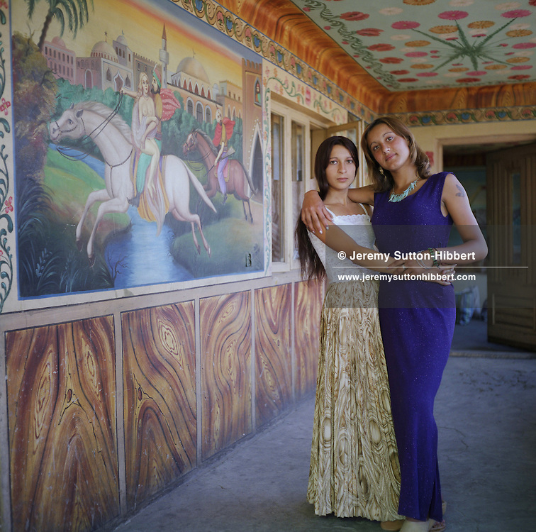 "Garoafa, wearing a ""western style"" purple dress, stands with her friend beside a scene from a Persian story painted on the wall of a Roma home, in the old part of the camp.  These Arabian scenes are very popular as wall decoration, but no-one within the camp knows the reason why they were first painted."