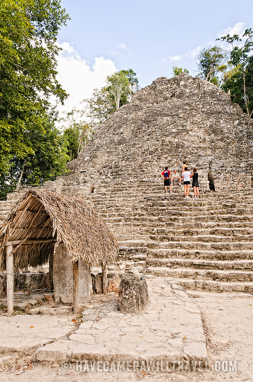 Tourists climb the 120 steps of the temple structure known as La Iglesia (The Church). The small structure with the thatched roof in the foreground has been designated as Stela 11. Coba is an expansive Mayan site on Mexico's Yucatan Peninsula not far from the more famous Tulum ruins. Nestled between two lakes, Coba is estimated to have been home to at least 50,000 residents at its pre-Colombian peak.