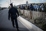 CRS (special french police forces) with pepper spray preventing migrant to get on the truks