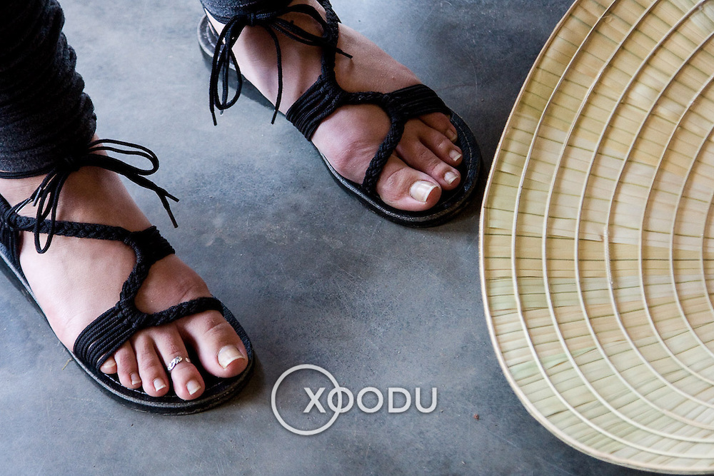 Closeup detail of feet in sandals near conical bamboo hat (Hue, Vietnam - Nov. 2008) (Image ID: 081111-1148541a)
