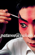 a Peking opera actor making up, China