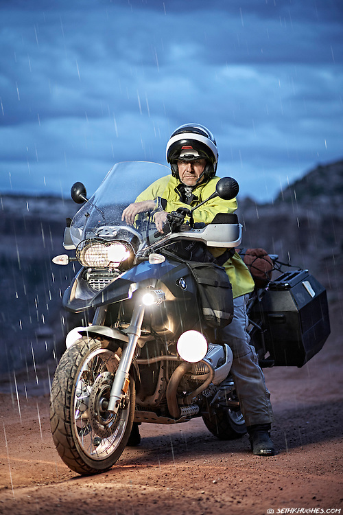 A man on a BMW GS motorcycle stands with his bike on the road in the rain at Canyonlands National Park, Utah.