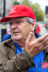 """Mike McFadden, 71, from London outside Parliament in a cap emblazoned with """"Drain the swamp!"""". London, September 24 2019."""