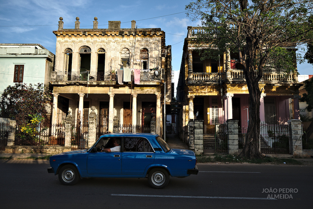 Small Lada from Soviet period passing by decaying occupied houses at the Vedado area.