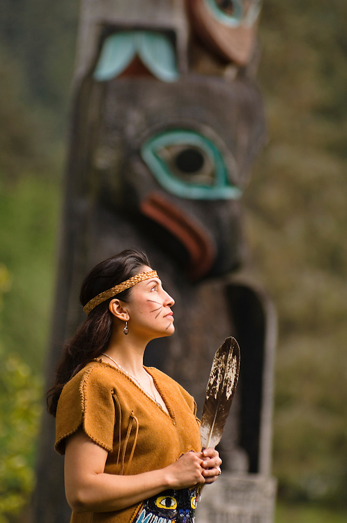 Wilma Leslie, native Alaskan woman of Tlingit and Haida ancestry, wearing traditional Tlingit dress, with totem pole in background, at Chief Shakes Island; Wrangell, Alaska.