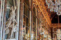 Ornate statues and golden brocade line the Hall of Mirrors in the Palace of Versaille, Paris, France