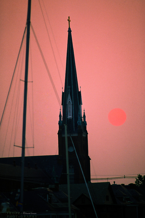 """Annapolis, Maryland--The mast of a sailboat contrasts the tower of St. Mary's Catholic Church at sunset. The church,built on the property of Revolutionary patriotCharles Carroll of Carrollton, the only Catholic signer of the Declaration of Independencewas concencrated in 1860.With its close proximity to the Chesapeake Bay andit's huge boating population. Annapolis is known as the """"Sailing Capital of the World."""""""