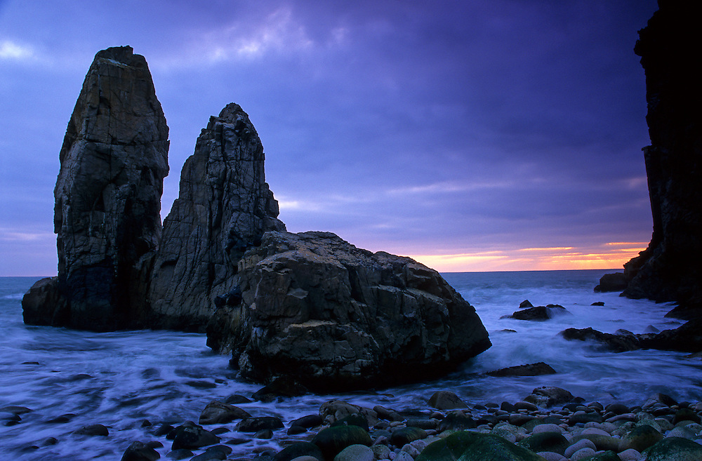 Two rock stacks stand on Malhada do Ourical, near Roca Cape, as the sun sets