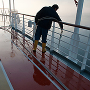 Worker hosing down a cruise ship at sunrise