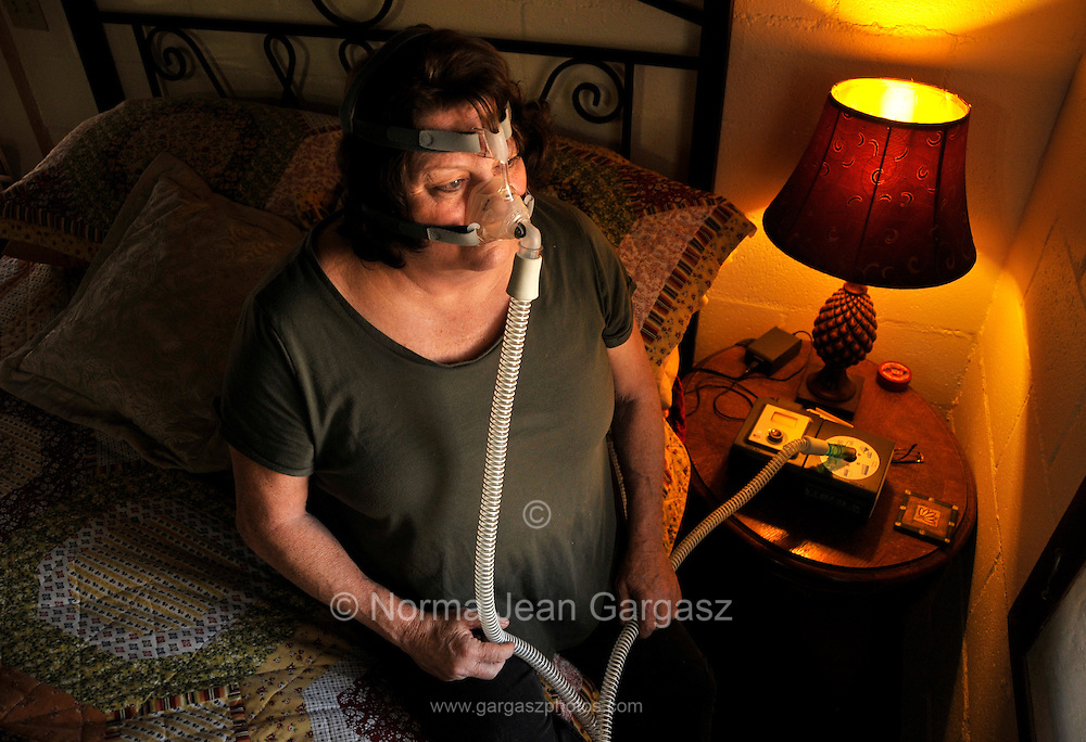 A chronically ill patient applies a bi-pap machine that delivers continuous air while sleeping for the treatment of sleep apnea.