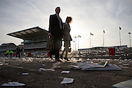 Two race goers making their way out of Aintree stadium through piles of litter at the end of the final day of the three-day Grand National meeting.