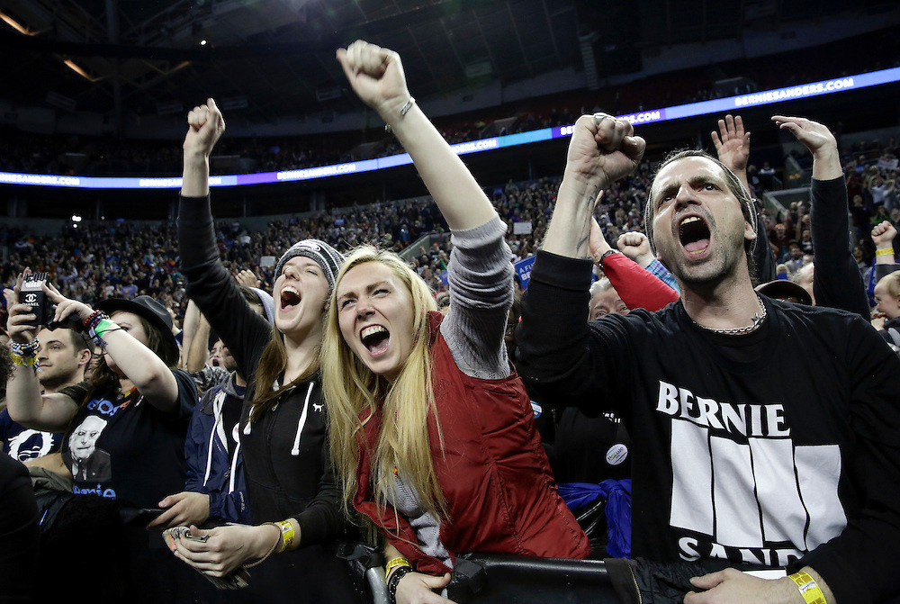 People cheer during a rally for Democratic presidential candidate Bernie Sanders at Key Arena on March 20, 2016 in Seattle.  AFP PHOTO/JASON REDMOND