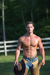 shirtless hunky cowboy holding his cowboy hat on a ranch