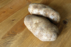 18 February 2016:   Studio - Potato #012.  A pair of baking potatoes rests uncooked on a wooden table top