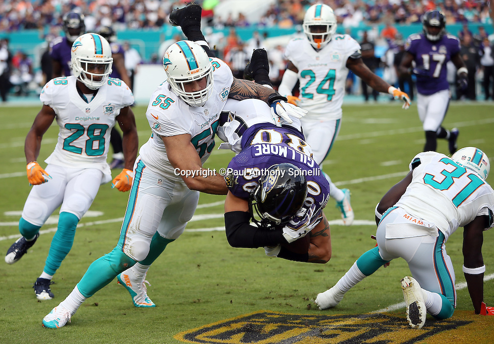Baltimore Ravens tight end Crockett Gillmore (80) gets upended by Miami Dolphins free safety Michael Thomas (31) and spun around in the air by Miami Dolphins outside linebacker Koa Misi (55) as he catches a third down pass for a first quarter first down at the Ravens 25 yard line during the 2015 week 13 regular season NFL football game against the Miami Dolphins on Sunday, Dec. 6, 2015 in Miami Gardens, Fla. The Dolphins won the game 15-13. (©Paul Anthony Spinelli)