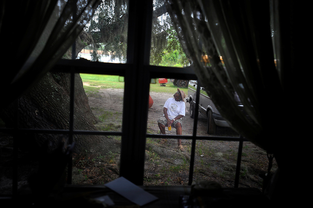 Watching for rain Cornelia Bailey sits in the yard outside her trailer-home in the Geechee-Gullah community of Hog Hammock, Thursday, Aug 23, 2012 in on Sapelo Island, Ga. Property owners are facing higher taxes, and fees from the county tax assessor, threatening an already fragile community. Bailey can trace her family's heritage back to slavery before the Civil War. (Stephen Morton for The New York Times)