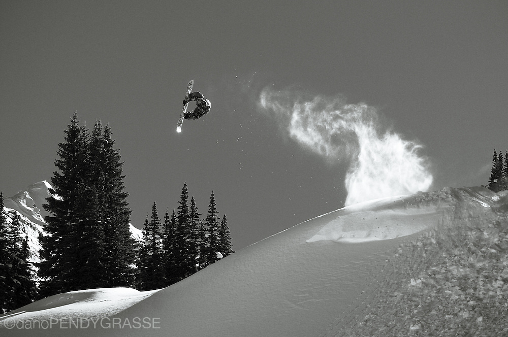 Professional snowboarder Romain de Marchi leaves a trail of powder in his wake as he flies through the skies of the Coast Mountains, British Columbia, Canada.