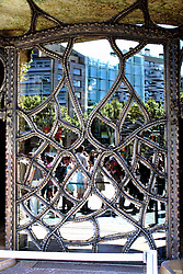 Intricate iron door reflecting the queue of tourists at La Pedrera, Barcelona.