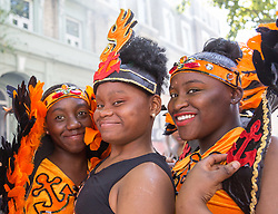 London, August 27 2017. Three girls await the start of the procession as Family Day of the Notting Hill Carnival gets underway. The Notting Hill Carnival is Europe's biggest street party held over two days of the bank holiday weekend, attracting over a million people. © Paul Davey.