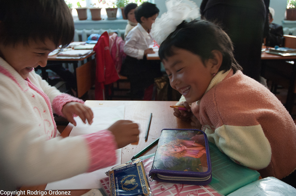Two girls laugh while they draw a picture at School 110 Boston, in Osh (Kyrgyzstan), where Save the Children supports a child-friendly space.