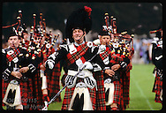 Pipe band marches on field as pipe major motions to straighten up lines @ Inverness Highland Games Scotland