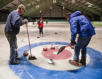 Sweepers Guy Knowlton, Sandra Ware and Mike Ware guide the positioning of the stones during the weekly curling tournament at the Gilford Ice Rink with Gilford Parks and Rec.  (Karen Bobotas/for the Laconia Daily Sun)