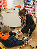 Sales associate Pam McLaughlin helps a young boy from the Laconia Girls and Boys Club try on his new shoes made possible with a $400.00 grant from Payless Shoes of Gilford Friday afternoon.   (Karen Bobotas/for the Laconia Daily Sun)