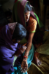 Radha, 15, has the wedding ritual of henna painted on her arms the day before the festivities begin, Rajashtan, India, April 26, 2009. Three young sisters Radha, 15, Gora, 13, and Rajni, 5, were married to their young grooms Aleen, Giniaj and Kaushal, who were also siblings, on the Hindu holy day of Akshaya Tritiya, called Akha Teej in north India. The auspicious day is said to bring good luck to couples married then and is widely known in Rajasthan as the day most child marriages occur. Despite legislation forbidding child marriage in India, such as the Child Marriage Restraint Act-1929 and the much more progressive Prohibition of Child Marriage Act of 2006, marrying children off at a very tender age continues to be accepted by large sections of society.