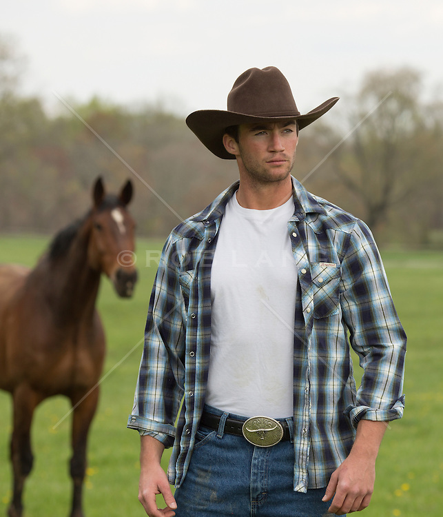 good looking cowboy with a horse on a ranch