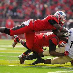 10 November 2012: Rutgers Scarlet Knights defensive back Lorenzo Waters (21) and linebacker Steve Beauharnais (42) tackle Army Black Knights running back Raymon Maples (1) during NCAA college football action between the Rutgers Scarlet Knights and Army Black Knights at High Point Solutions Stadium in Piscataway, N.J..