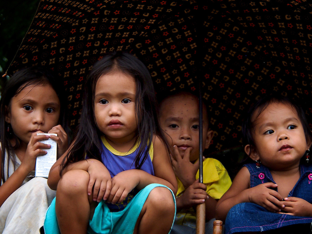 Along the Guinobatan River, small-scale miner dig sand from the river bottom to process into gold while children watch from the nearby river bank...Story Summary:.Small-scale gold mining in the Philippines uses mercury and cyanide to extract elemental gold from ore extracted from mines and pits dug by hand.  Very young children, some as young as four, are put to work at less dangerous but still rigorous tasks in the gold mining areas.  These include panning in streams or rivers and hauling ore sacks that can weigh up to 60 pounds.  Children often play near mechanized equipment and highly toxic mercury and cyanide.  These chemicals, used to help extract elemental gold from ore, are leached into nearby watersheds where fish and other marine life, mainstays of the Philippine diet, are poisoned.  The high price of gold and the poor economy in many developing countries has led to an increase in small-scale gold mining throughout the world.