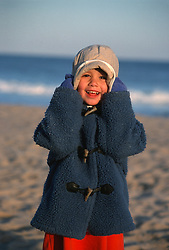 girl smiling and pulling down her hat while standing on the beach in East Hampton, NY