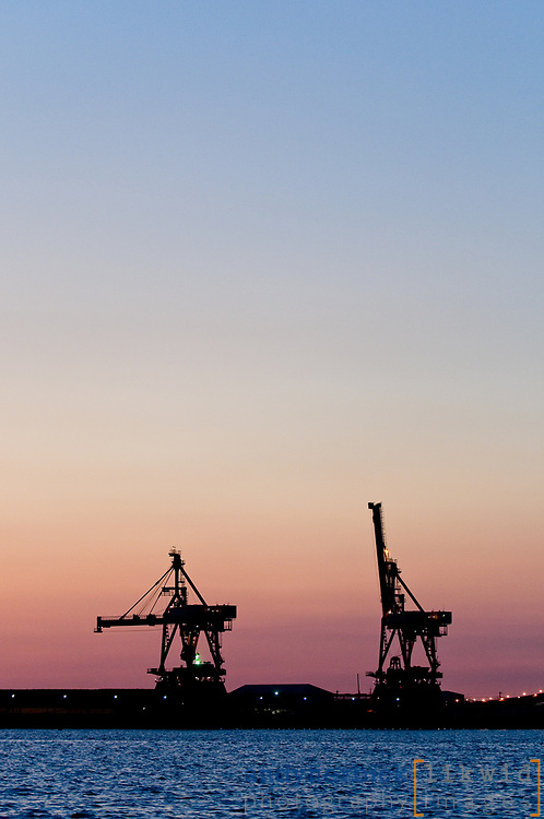 Cargo cranes at Bethlehem Steel silhouetted against a sunset sky