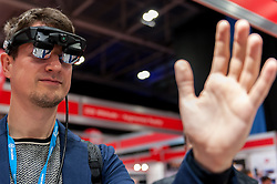 © Licensed to London News Pictures. 15/03/2016. London, UK. A man tries on a set of augmented reality glasses and is raising his hand to try to interact with the image he can see.  Technology fans visit the Wearable Technology Show at the Excel Centre.  The largest dedicated event for connected technology, the show features innovative products from start-ups as well as products from major technology companies and includes the latest in virtual reality and augmented reality devices and software. Photo credit : Stephen Chung/LNP