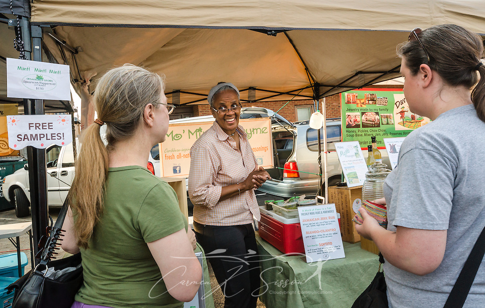 Lynn Porter, co-owner of Mo' Mint & Thyme, talks with customers about the company's all-natural drink and cocktail mixes during the Tucker Farmers Market in downtown Tucker, Georgia, May 22, 2014. The farmers market is held every Thursday from 4-8 p.m. during the growing season. It features products from local farmers and artisans. (Photo by Carmen K. Sisson/Cloudybright)