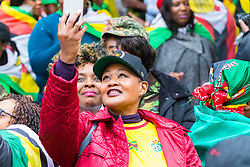 London, November 18 2017. Exiled Zimbabweans of all races gather outside the Zimbabwe Embassy in London to celebrate the military intervention in Zimbabwe and the apparent military ousting of dictator Robert Mugabe. The gathering coincides with a large march in Harare and other centres around the world where Zimbabwe's estimated 3 million exiles have moved to. © Paul Davey