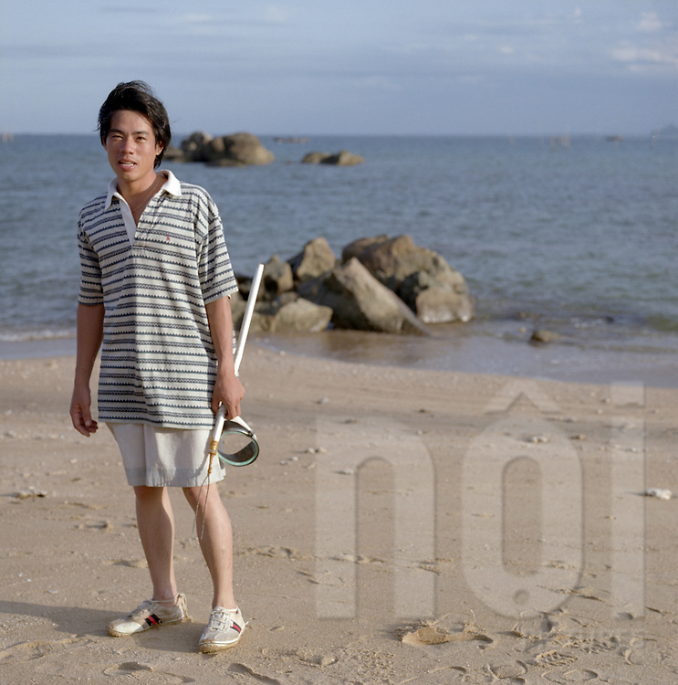 Young Vietnamese man stands on My Khe Beach with fishing gear, Da Nang, Vietnam, Southeast Asia